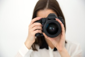 Woman photographer with camera over gray background, Using Photographs for your Accounting Website